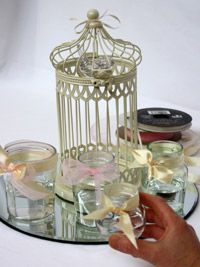 decorating jam jars with ribbon bows for a wedding centerpiece