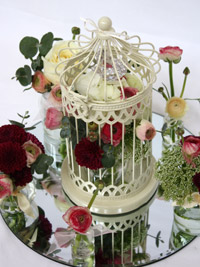 flowers arranged around a birdcage for a vintage style wedding centerpiece