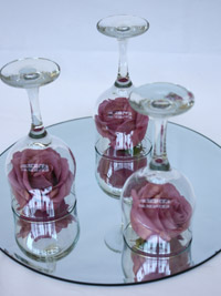 wine glasses with roses placed on a circular mirror centerpiece