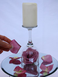 adding rose petals and a candle to a diy centerpiece