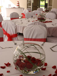 red roses floating in a large goldfish bowl to create a low diy centerpiece