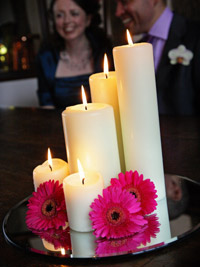 large chapel candels decorated with flowers to create a wedding centerpiece