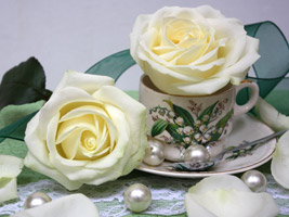 roses in vintage cups and saucers used for wedding reception decorations