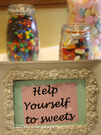 a sign saying help yourself at a wedding candy bar