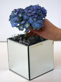 adding blue hydrangea flowers to a low centerpiece
