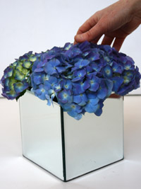 packing blue wedding flowers into a low centerpiece
