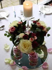 arranging wedding flowers around a candle to create a centerpiece