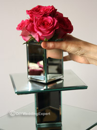 placing a pink rose topper on the top tier of a wedding cupcake stand