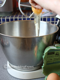 adding eggs to a mixer when making diy wedding cupcakes