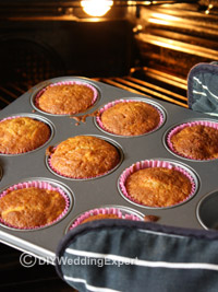 cupcakes being taken out of the oven