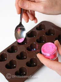 adding pink edible glitter to diy wedding favor chocolates