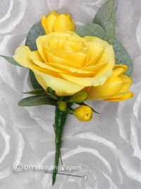 grooms yellow buttonhole featuring a rose and freesias